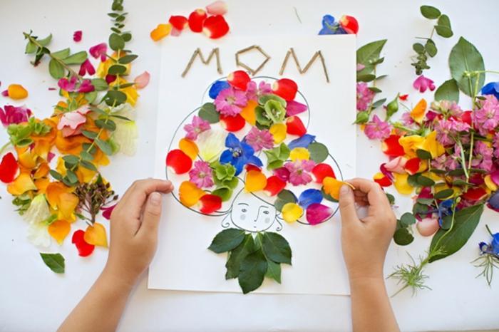 carte de voeux pour la fete des mères dessin et matériaux naturelles, des pétales de fleurs multicolores, visage femme maman, cadeau fete des meres