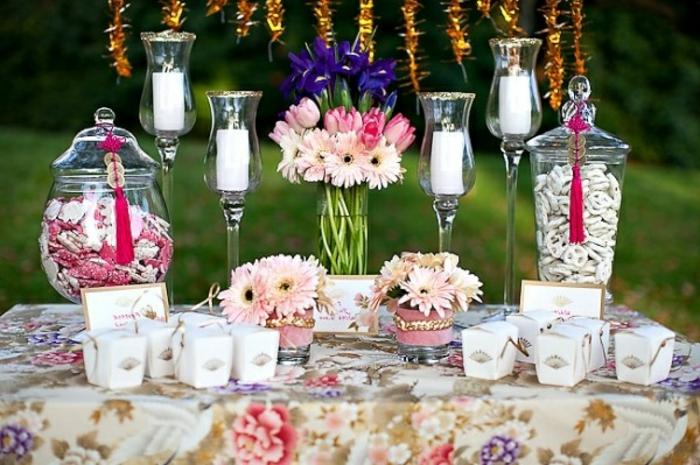 bonbons de sucre, bouquets de fleurs de tailles diverses, bougeoirs, nappe à motifs floraux, cadre naturel, mariage en plein air