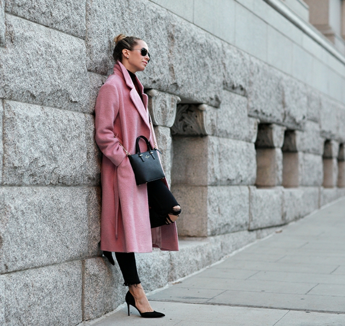 jean noir déchiré femme, manteau long en rose, chignon blond, sac à main en cuir, chaussures noires