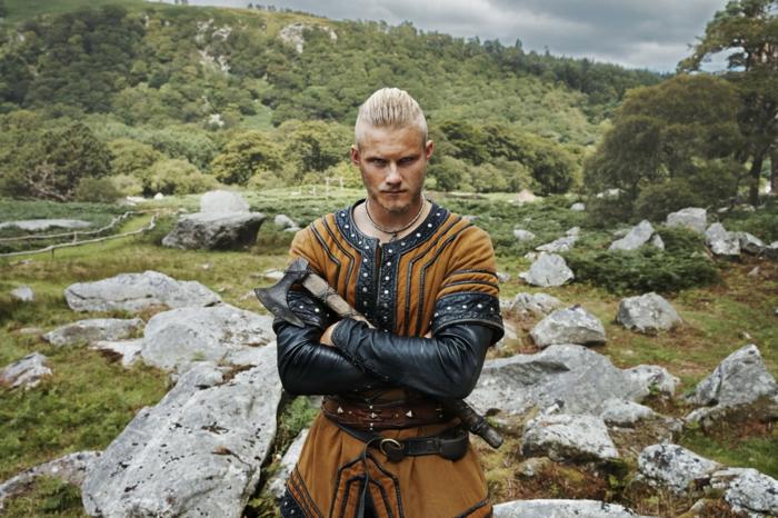 coupe de cheveux viking, bjorn lorthbrok, man bun, collier ethnique, chemise marron en cuir noir