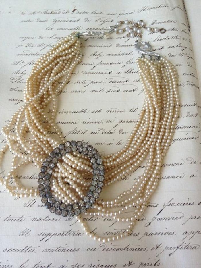 collier de perles avec un grand élément ovale devant en pierres synthétiques blanches