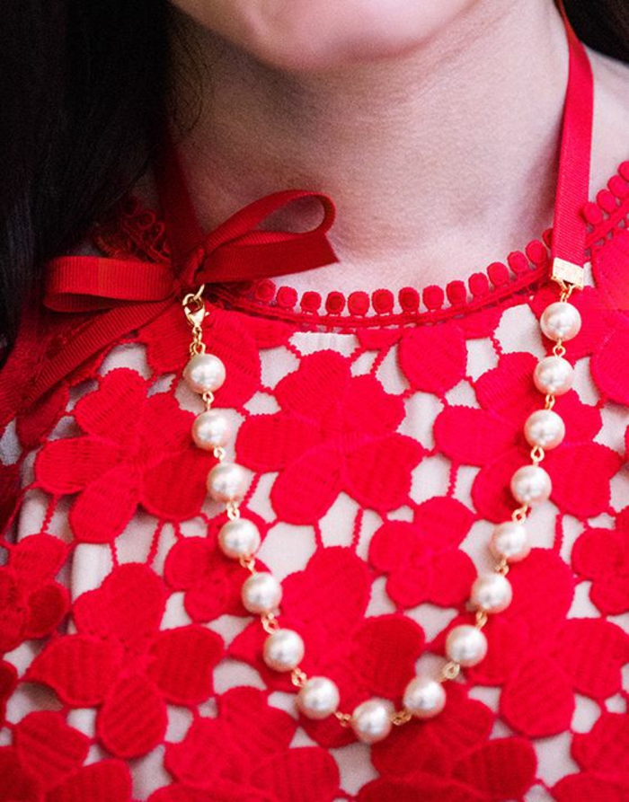 collier de perles sur top rouge aux fleurs effet ciselé sur le tissu