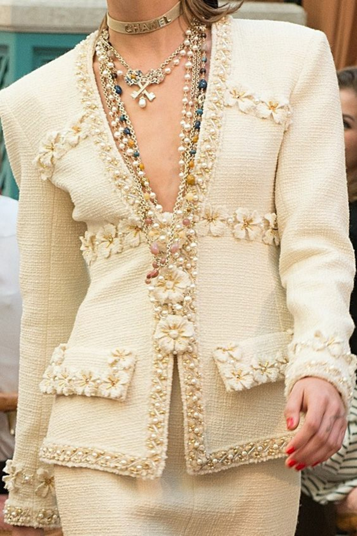 collier de perle sur un ensemble couleur champagne de Chanel et trois fleurs de tissu devant