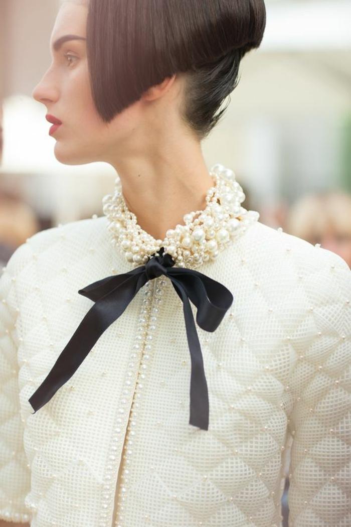 collier perles culture se terminant en tissu en satin noir sur une veste matelassée blanche Chanel ornée de perles sur les revers de Chanel