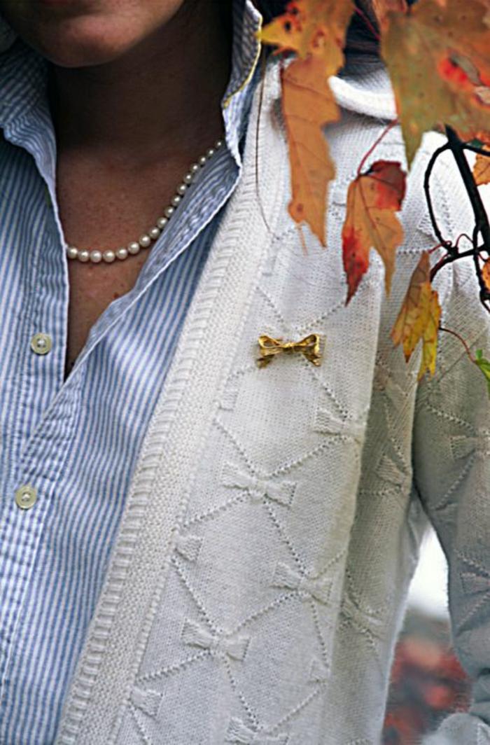 collier de perles porté avec une veste blanche aux motifs noeuds repris sur la broche en métal jaune