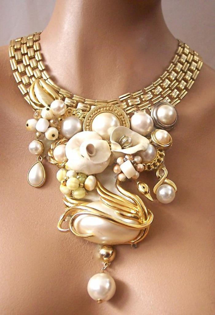 collier en perle en métal doré avec des motifs nature cygne et fleurs blanches