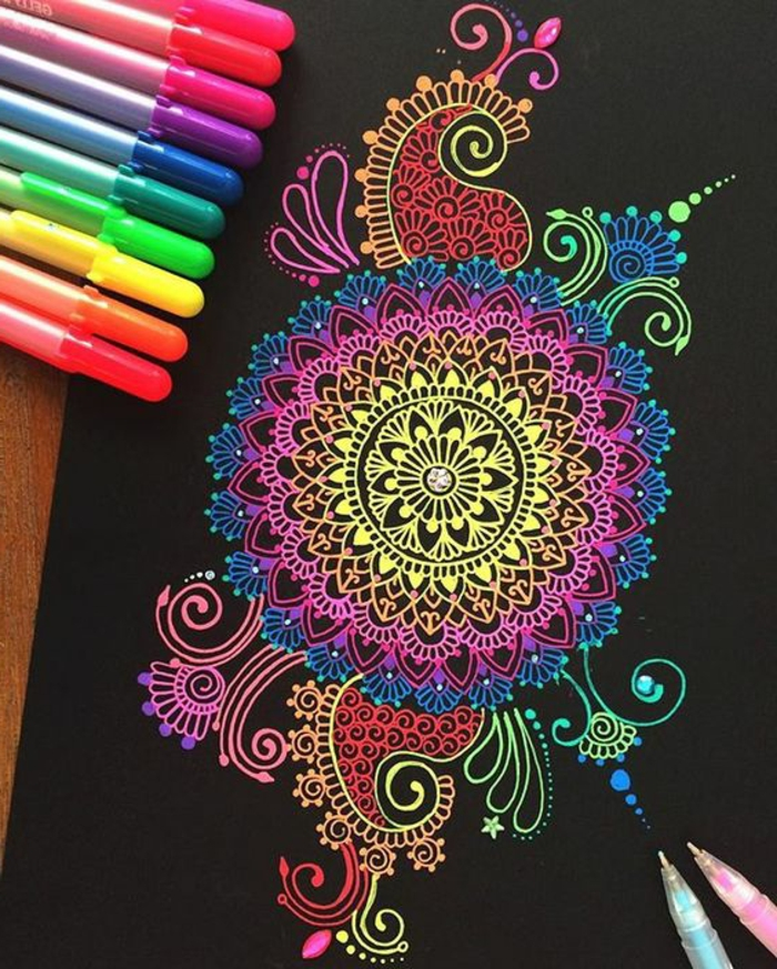 mandala facile a faire, crayons, papier noir, mandala multicolore, motifs floraux, volutes, cercles, schème mandala