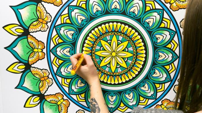 mandala à colorier, fleur jaune, feuilles vertes, volutes, papillons jaune et orange, filles, tatouage sur main
