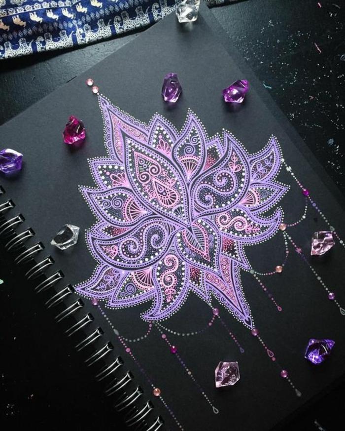 petit mandala, décoration sur la couverture noire, cahier, cristaux violets, nappe bleu et blanc, table noire