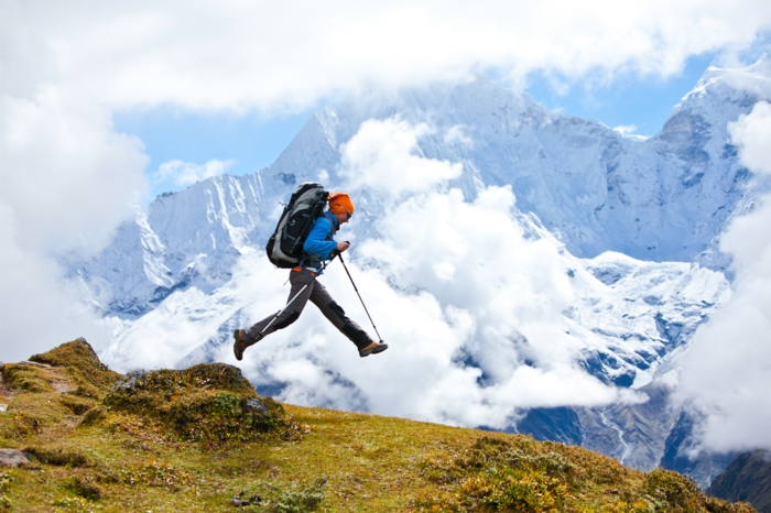 entrainement sportif, montagnes, sac à dos, bonnet orange, veste bleu, bâton télescopiques