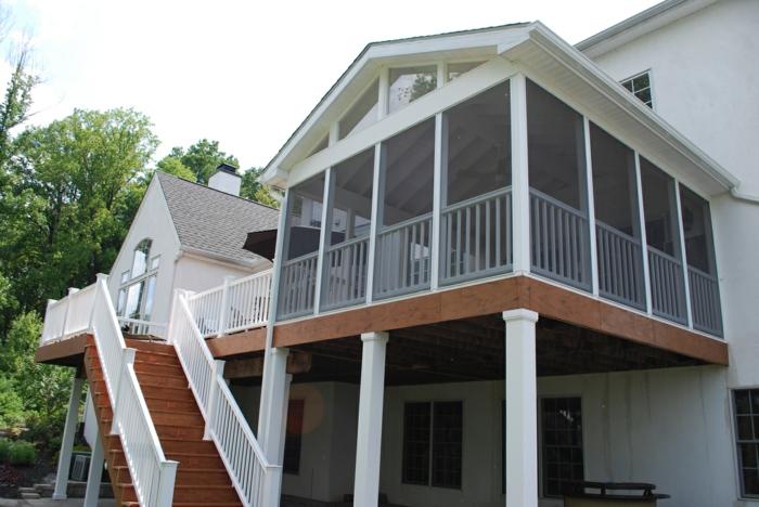 terrasse surélevée, maison à façade blanche, escalier en bois, rambarde blanche, fenêtres à carreaux