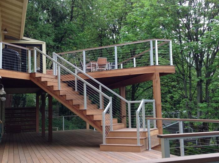 terrasse bois sur pilotis, escalier en bois, rambarde en métal peint en blanc, salon de jardin en bois, vue sur la forêt