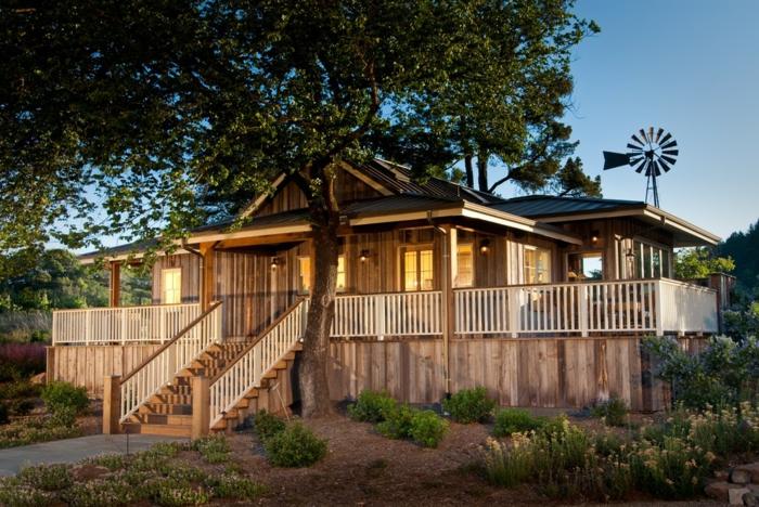 terrasse bois surélevée, fleurs jaunes, jardin, plantes vertes, lanternes d'extérieur, maison en bois
