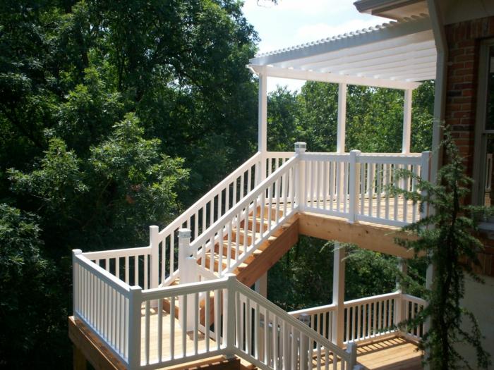 terrasse sur pilotis, arbres, escalier en bois, auvent en bois peint en blanc, façade en briques