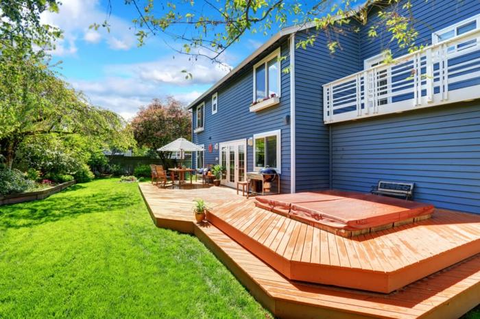 terrasse surélevée, ray grasse, façade bleue, pot à fleurs céramique, parasol blancs, salon de jardin en bois