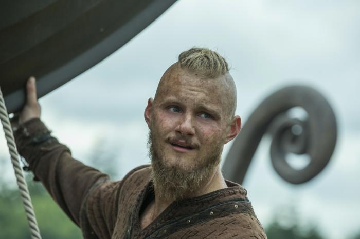 coiffure viking, Bjorn Lorthbrok, undercut, man bun, cheveux blonds, yeux bleus, chemise marron