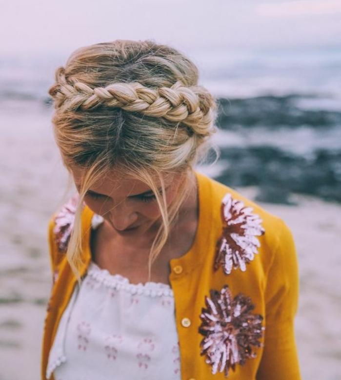 tresse couronne, coiffure bohème, cheveux blonds, mèches de cheveux tombantes, plage, gilet jaune ocre à fleurs rouges paillettés