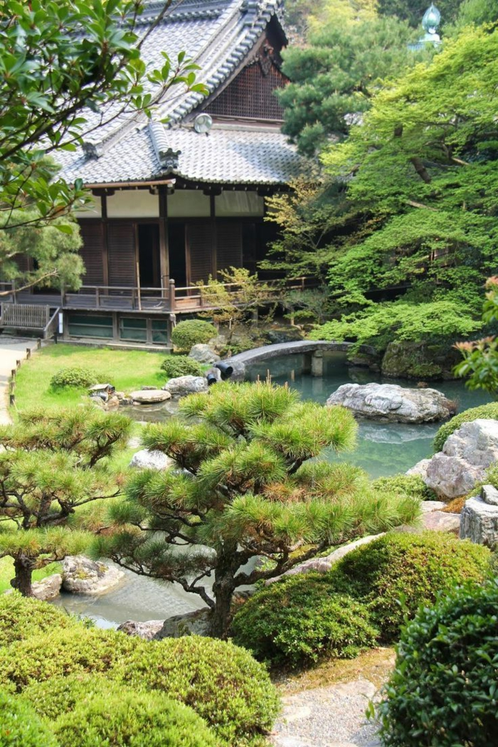 parterre de fleurs avec galets, arbres verts, bassin d'eau, petit pont en béton, gazon vert