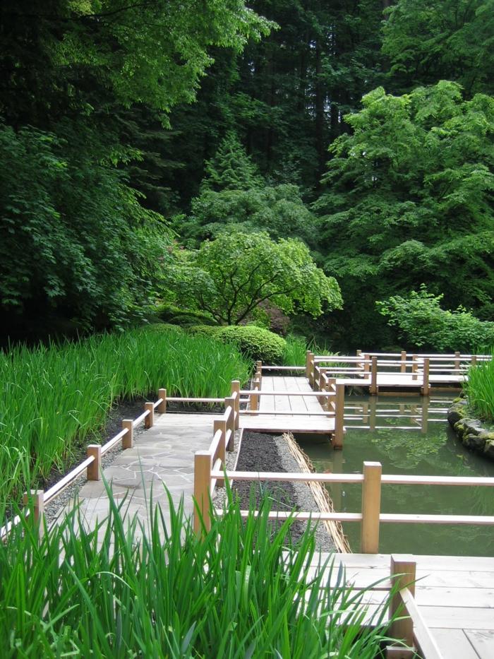 jardin zen japonais, pont zig zag en bois, gazon vert, arbres verts, bassin d'eau
