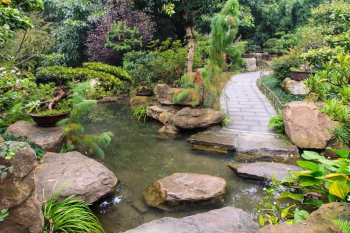 déco de jardin zen, bassin d'eau, pont, rochers dans l'eau, broussailles vertes, jardin zen