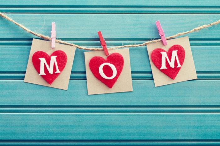 des coeurs en feutrine rouge avec des lettres maman, suspendus par des pinces à linge, cadeau pour la fête des mères
