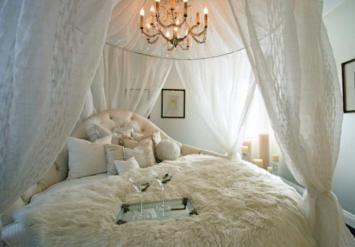 chambre boudoir, voiles blanches, tête de lit capitonné, cadres photos noires, murs blancs, bougies