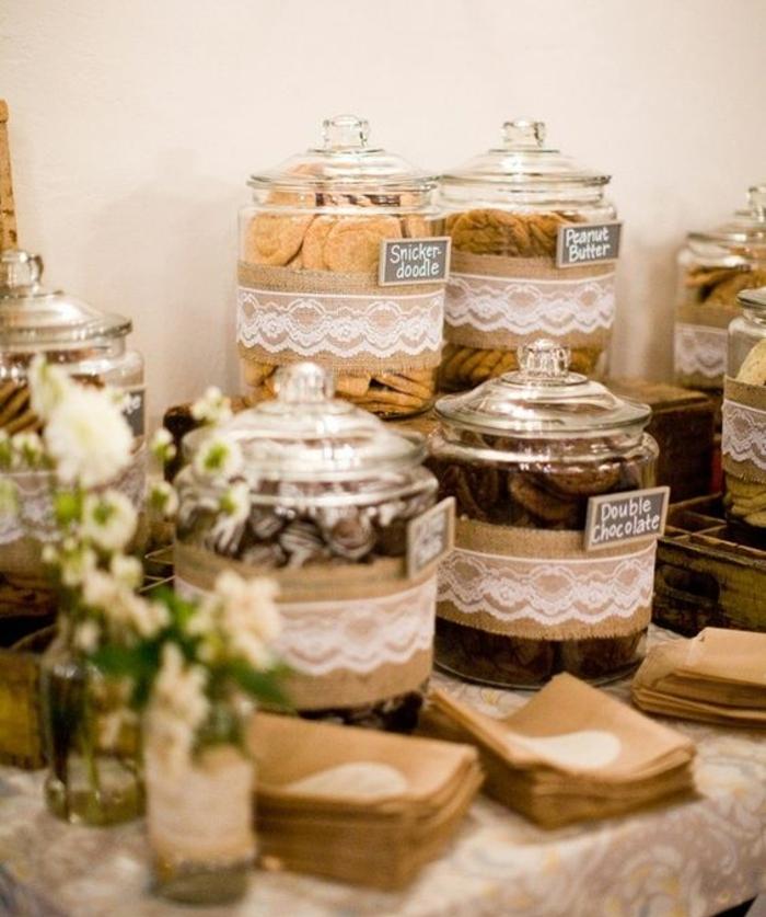 sablés, biscuits rangées dans des bonbonnières, decoration abr a bonbon en marron et beige, bouquets de fleurs blanches, nappe à motifs divers