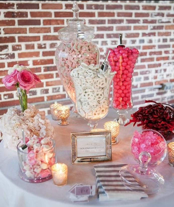 bar à bonbons mariage, nappe blanche, dragées et boules de gomme et bonbons de sucre en rose et blanc, cadre photo argenté, bougeoirs en verre, table de fond en briques