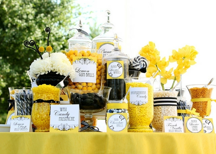 dragées et sucettes en noir, blanc et jaune, nappe jaune, étiquettes, fleurs jaunes, idee deco mariage en plein air, candy bar mariage