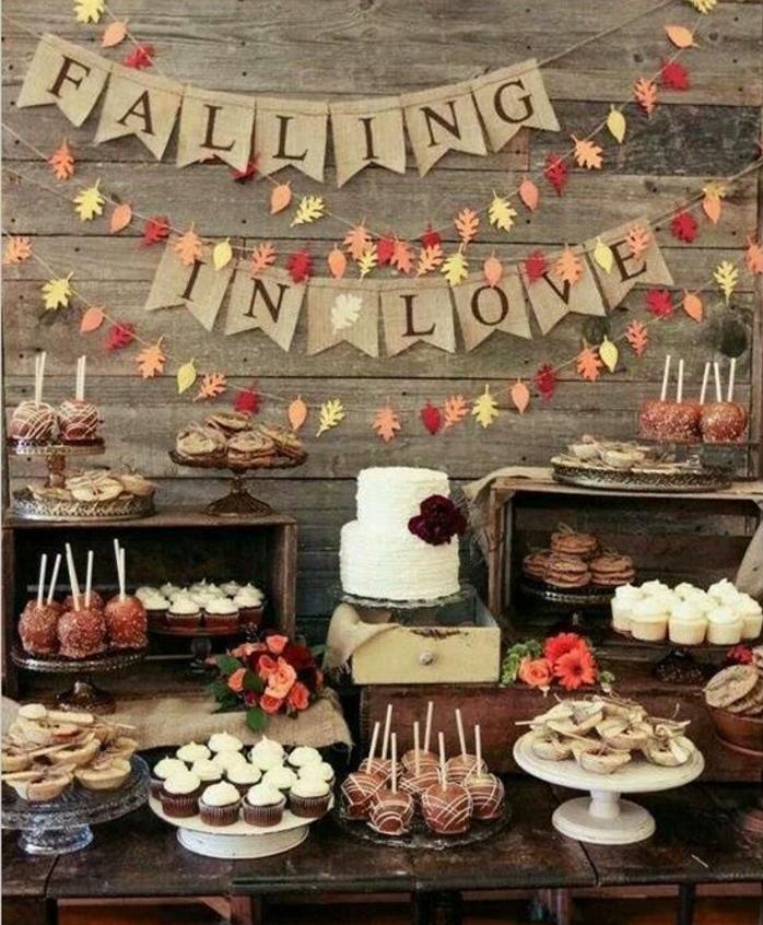 decoration bar a bonbon, cupcakes, sablés, tartalettes, pommes d amour chocolat, gateau à deux étages, guirlande de feuilles mortes en papier, et guirlande en tissu intéressant, table en bois, mariage vintage rustique