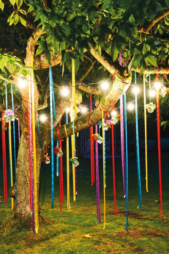 idee deco jardin a faire soi meme, guirlande lumineuse en ampoules, ruban long multicolore, arbre dans le jardin