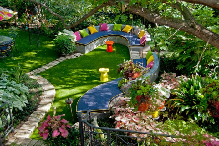 recup jardin, clôture en fer forgé, sentier en pierres, banc en tissu bleu, parasol multicolore, salon de jardin, table en verre