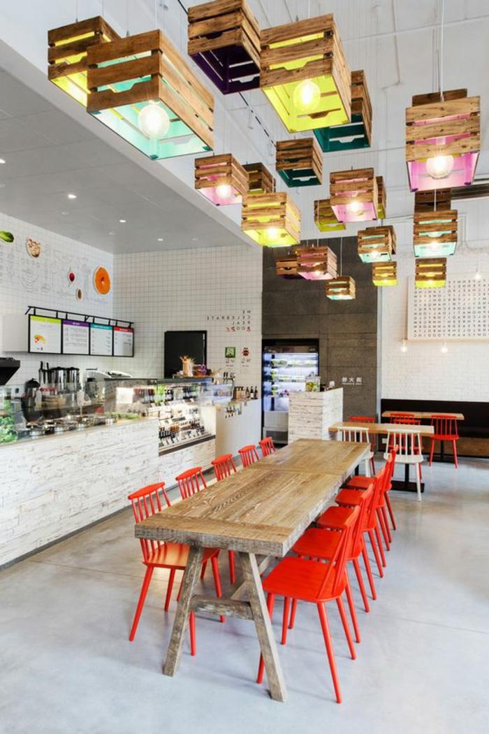 caisses en bois transformés en abat-jours, idée déco luminaire rustique chic, design dans un resraurant univeritaire, table en bois longue, chaises en métal rouges