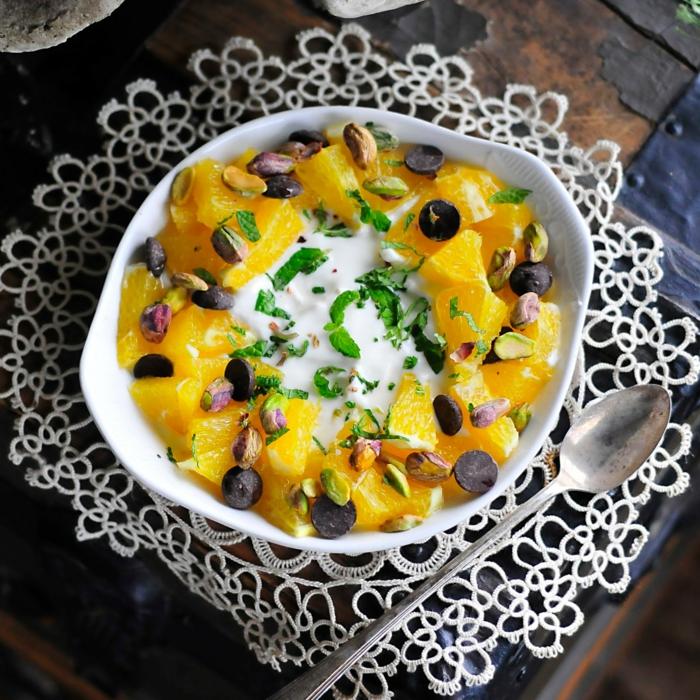 dessert peu calorique, yogourt, morceaux d'orange, feuilles de menthe, cuillère à dessert, bol blanc