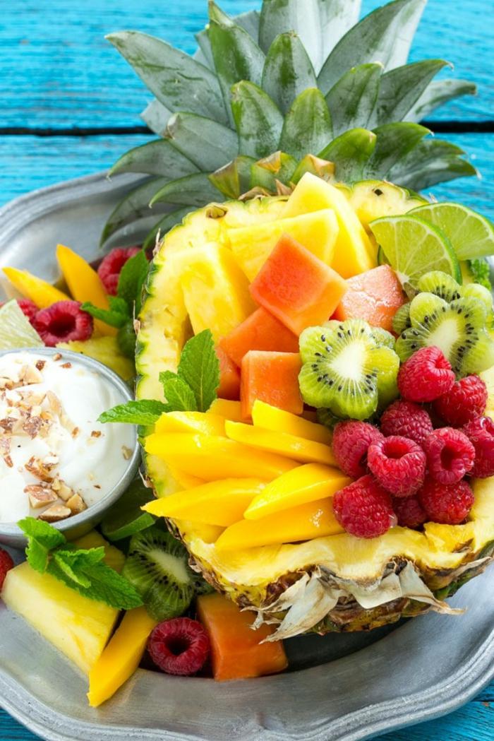 dessert léger et rapide, kiwi, yogourt, noix hachées, ananas, fraises, table peint en bleu, assiette grise