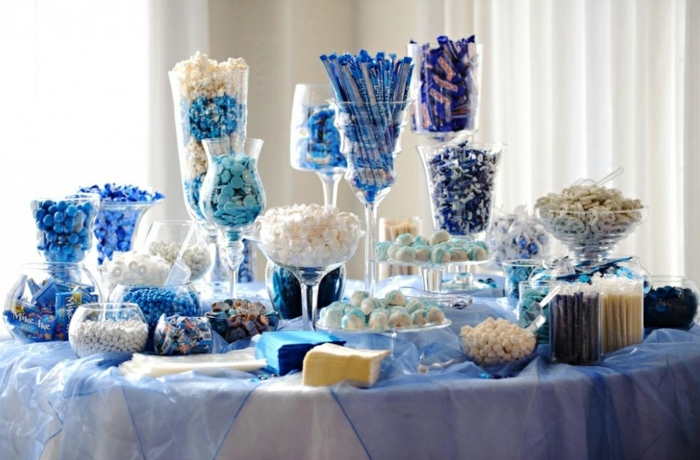 bonbons, dragées, pistilles, réglisses, desserts chocolat, bonbons de sucre en blanc et bleu, table ronde, nappe blanche, voile bleu, decoration bar a bonbon thématique