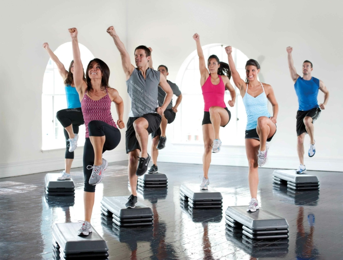 sport pour maigrir, salle de gym blanche, step fitness, banc de step, shorts noirs, legging noir, baskets gris et rose