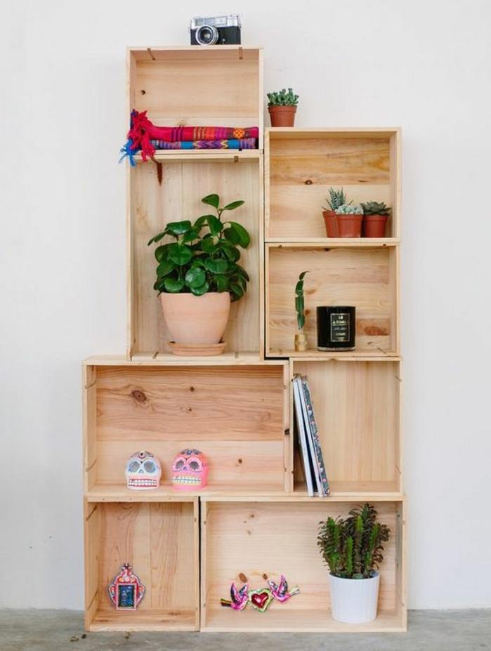etagere cagette asymétrique en bois, plusieurs caisses rangées de maniere asymétrique, rangement plantes, accessires deco, appareil photo vintage, livres, couvertures de lit