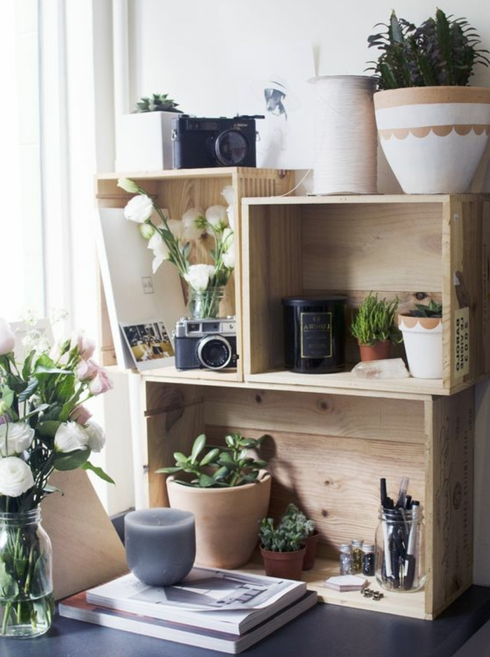 modele etagere cagette sur un bureau, plantes vertes, appareil photo vintage, livres, bouquet de fleurs, bougies, pot à crayons