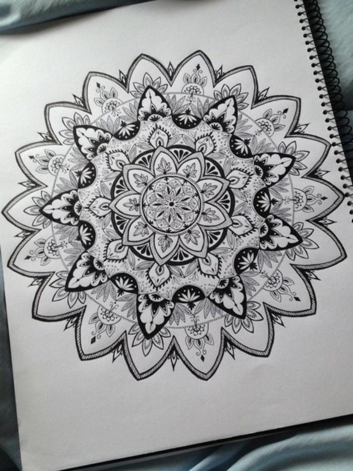 mandala facile a faire, cahier blanc, nappe bleu clair, mandala blanc et noir, motifs floraux