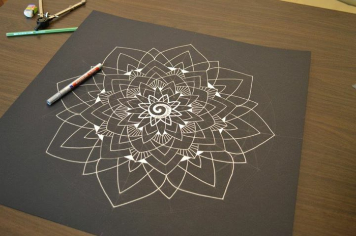 mandala facile a faire, papier noir, crayons, gomme à effacer, table en bois, schème mandala blanc