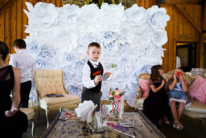 une décoration murale pimpante en roses de papier qui sert d'un cadre photobooth