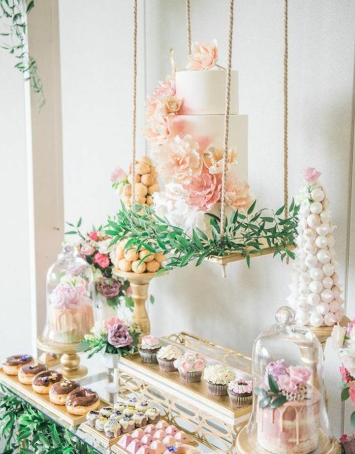 gateau de mariage, décoré de fleurs sur un balançoire, cupcakes, donuts, petits gateaux, meringues, bonbons, decoration bouquet de fleurs et branches vertes, candy bar mariage
