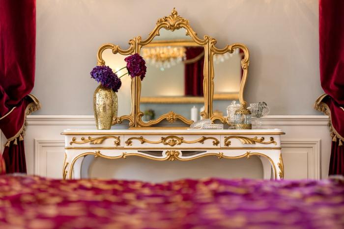 chambre boudoir, coin de maquillage, miroir doré, rideaux longs rouges, murs blancs, vase dorée, fleurs violettes