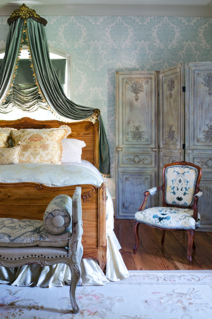 amenagement chambre, murs damassés en bleu, rideaux verts, lit en bois, coussins orange, chaise en bois