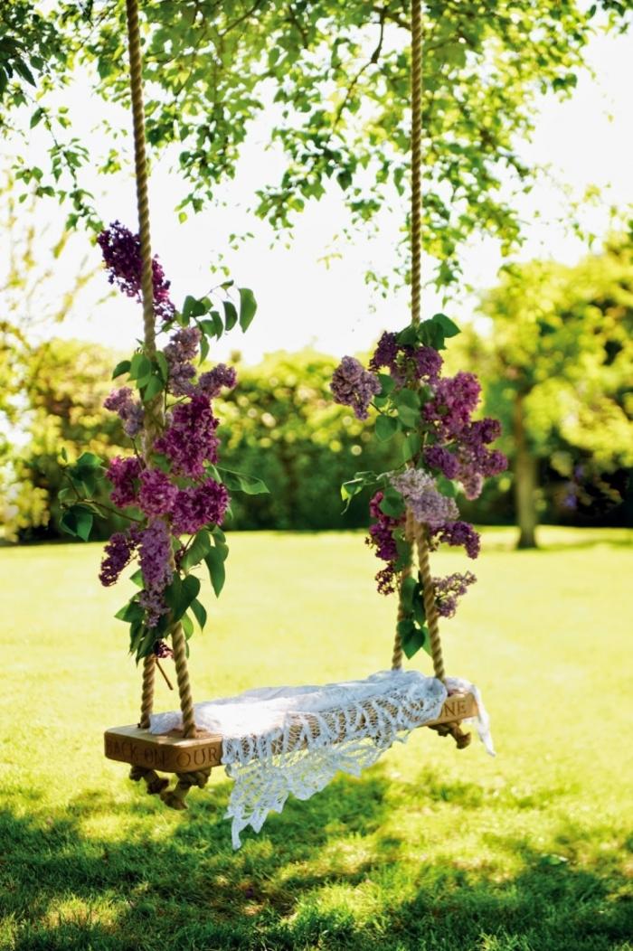decoration exterieur de jardin, balançoire en bois, corde décorés en lilas, arbres, gazon vert