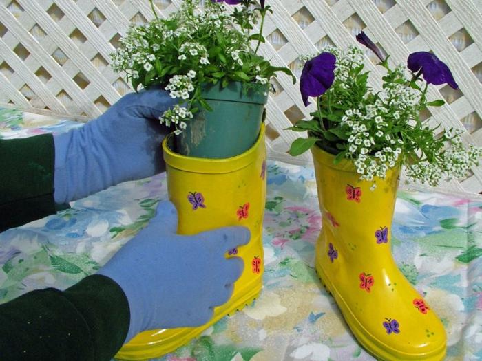 decoration de jardin a faire soi meme, bottes en caoutchouc jaunes, motifs papillons, plantes vertes, gants bleus
