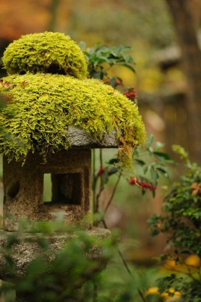 objets decoration jardin, lanterne en pierre couverte de mousse, broussailles vertes, déco de jardin zen