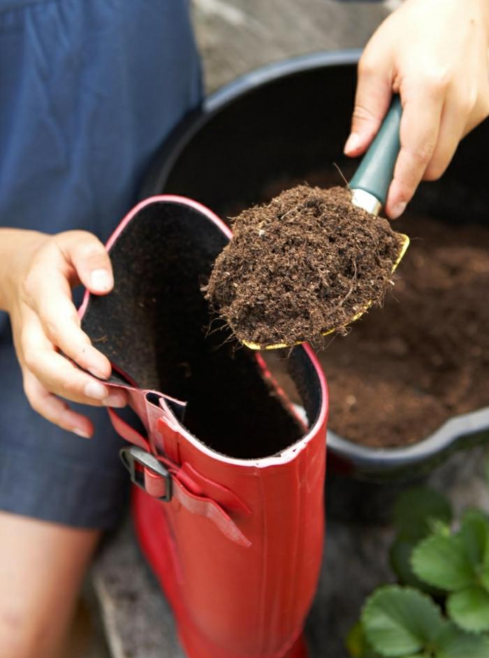decoration de jardin a faire soi meme, déplantoir gris et jaune, bottes en caoutchouc rouge