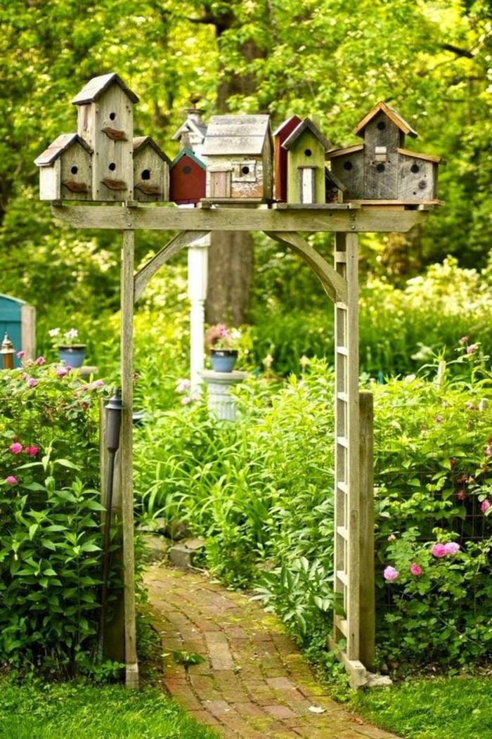 amenagement jardin, porte en bois, étagère avec mangeoires d'oiseaux, plantes vertes, sentier en pierre